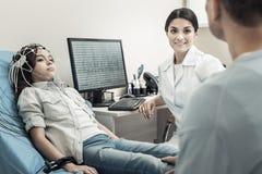 Gentil docteur positif s'asseyant devant l'ordinateur Image libre de droits