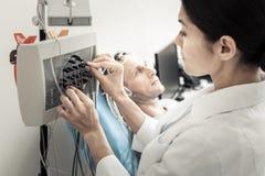 Gentil docteur professionnel installant l'électro-encéphalographe Image stock