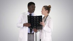 Gentil docteur sérieux de femme et raie afro-américain du cerveau X d'étude de docteur sur le fond de gradient banque de vidéos