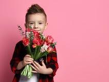Gentil enfant de petit garçon dans la chemise rouge avec un grand bouquet des fleurs de ressort prêtes à féliciter avec un jour d photos libres de droits
