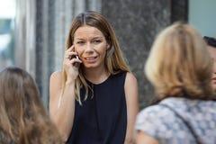 Gentil, Frances le 15 août 2017 : Fille blonde parlant au téléphone portable dans le secteur de rue commerciale Images stock