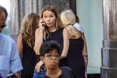 Gentil, Frances le 15 août 2017 : Fille blonde parlant au téléphone portable dans le secteur de rue commerciale Image stock
