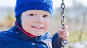 Gentil garçon de sourire sur une oscillation photos stock