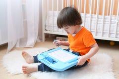 Gentil garçon en peintures oranges de T-shirt sur le comprimé magnétique à la maison Photos stock