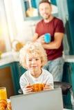 Gentil garçon heureux tenant un croissant Photo libre de droits