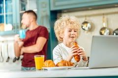 Gentil garçon positif mangeant un croissant Photos libres de droits