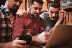 Gentil groupe agréable d'amis s'asseyant à l'ordinateur portable Images libres de droits