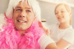 Gentil homme agréable laissant sa fille faire sa coiffure Photographie stock