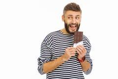Gentil homme bel mordant une barre de chocolat images libres de droits