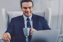 Gentil homme d'affaires agréable tenant une tasse de thé photo stock