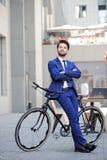 Gentil homme d'affaires se penchant sur la bicyclette images stock