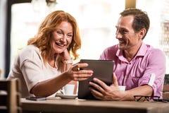Gentil homme et femme tenant le comprimé numérique Photographie stock