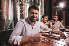 Gentil homme gai mettant un verre avec de la bière sur la table Photographie stock libre de droits
