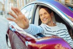 Gentil homme joyeux ondulant de la fenêtre de voiture Photos libres de droits