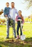 Gentil homme joyeux se tenant avec ses enfants Images stock