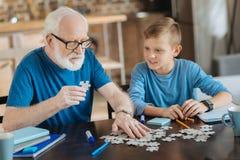 Gentil homme plus âgé tenant un morceau de puzzle Photos stock
