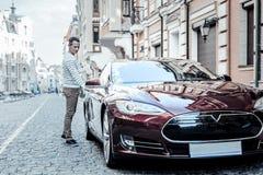 Gentil homme positif ouvrant la voiture Image stock