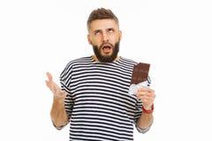 Gentil homme sceptique tenant une barre de chocolat photo libre de droits