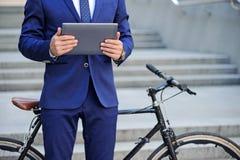 Gentil homme tenant l'ordinateur portable près de la bicyclette image stock