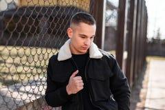 Gentil jeune homme beau dans une veste noire à la mode avec la fourrure avec une coiffure à la mode dans les supports élégants no image libre de droits