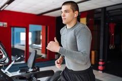 Gentil jeune homme costaud, occupé dans les sports, tapis roulant, exercice de matin photos stock