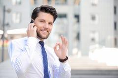 Gentil jeune homme d'affaires tenant le téléphone portable image stock