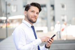 Gentil jeune homme d'affaires tenant le téléphone portable images libres de droits