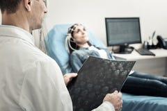Gentil neurologue expérimenté étudiant son cerveau de patients Photos libres de droits