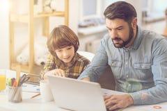 Gentil père beau à l'aide d'un ordinateur portable Images libres de droits