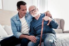 Gentil père et fils réfléchis s'asseyant ensemble Image stock