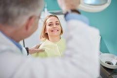 Gentil patient féminin souriant dans la chaise dentaire images stock