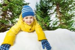 Gentil petit garçon en jaune sur le sourire de mur de neige Photo stock