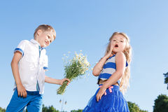 Gentil petit garçon présent des fleurs Images stock
