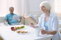 Gentil retraité gai lisant un livre Images stock