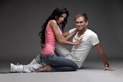 Gentil type agréable avec la fille sur le fond gris Photographie stock libre de droits