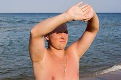 Gentil type louchant au soleil sur la plage Images libres de droits