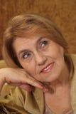 Gentille dame âgée s'asseyant sur un sofa Photographie stock libre de droits