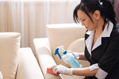 Gentille domestique sérieuse d'hôtel nettoyant le sofa photo libre de droits