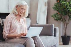 Gentille femme âgée à l'aide de son ordinateur portable à la maison Photos libres de droits
