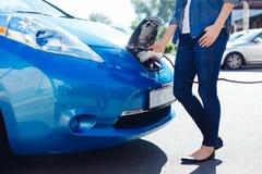 Gentille femme agréable branchant un électro chargeur à la voiture Images stock