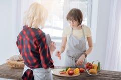 Gentille femme agréable préparant le dîner sain Photographie stock libre de droits