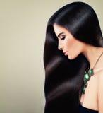 Gentille femme avec de longs colliers de cheveux et de bijoux photographie stock