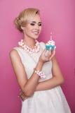 Gentille femme blonde tenant le petit gâteau avec la bougie Anniversaire, vacances Photo stock