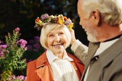 Gentille femme d'une chevelure grise heureuse recevant le cadeau photographie stock