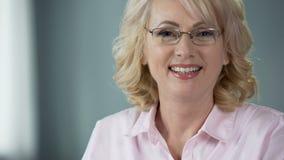 Gentille femme d'une cinquantaine d'années mettant sur des verres souriant dans l'appareil-photo, vue saine banque de vidéos