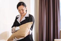 Gentille femme de chambre agréable tenant le coussin image libre de droits