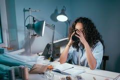 Gentille femme en verres avec le thé potable de cheveux de curlu à la table dans l'atelier Images libres de droits