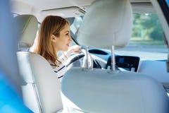 Gentille femme futée s'asseyant dans la voiture Image stock