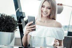 Gentille femme gaie à l'aide de son smartphone Photographie stock libre de droits