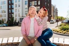 Gentille femme joyeuse fermant ses yeux de maris Images stock